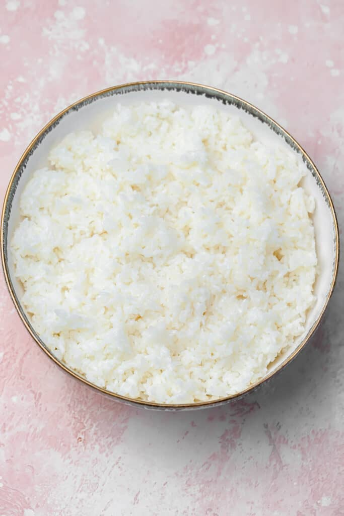 Sushi rice in a white bowl with seasoning