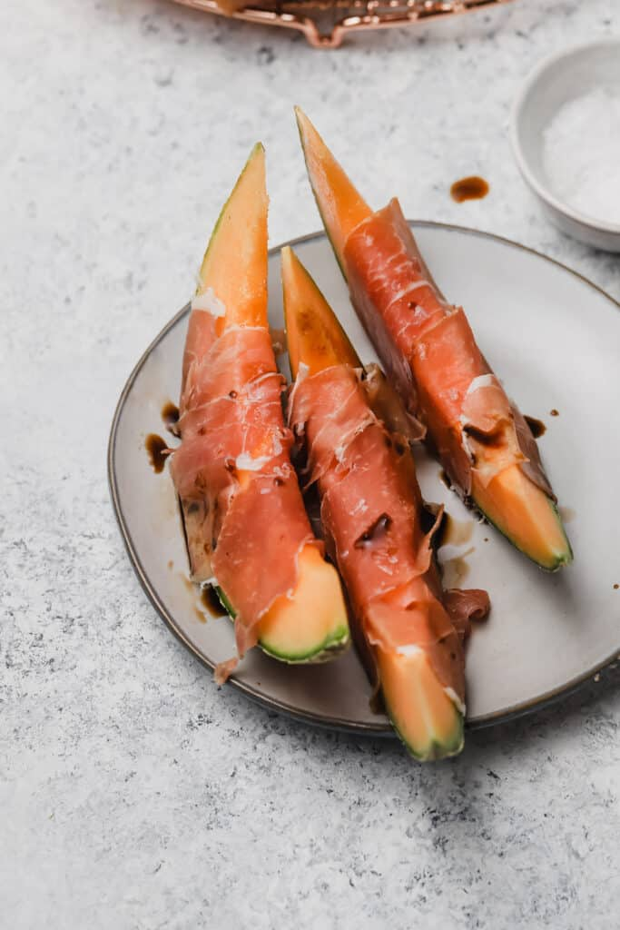 Three prosciutto wrapped cantaloupe wedges on a plate
