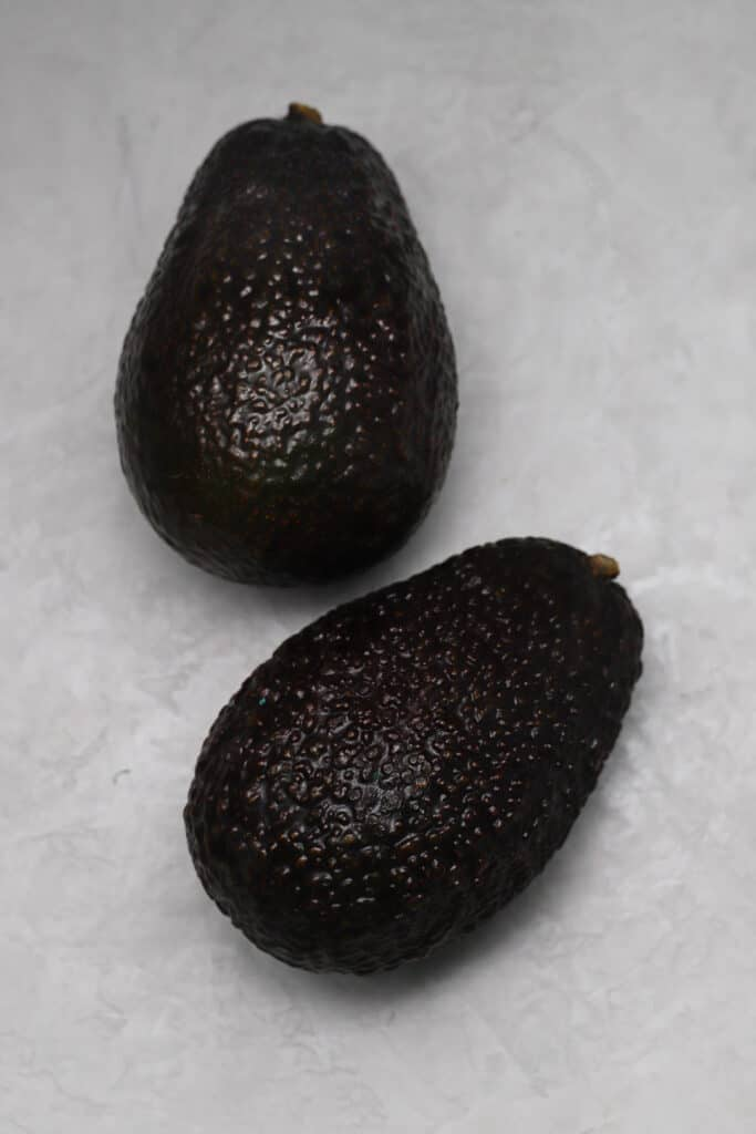 Two avocados on a gray board