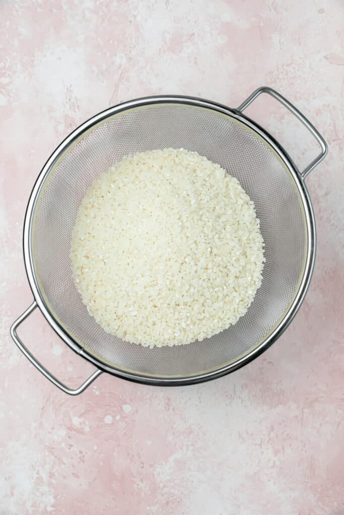 Uncooked rice in a strainer