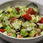 avocado tomato salad with scallions in a bowl