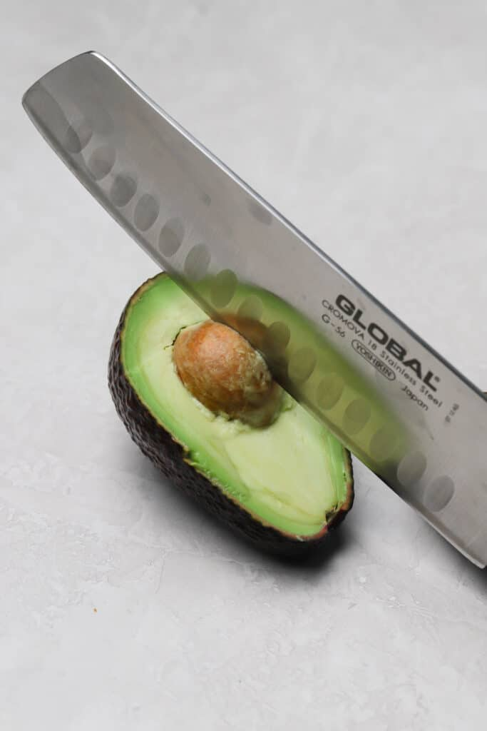 removing the pit of an avocado with a chefs knife