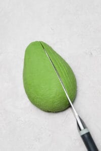 slicing an avocado thinly with a paring knife