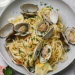 spaghetti alle vongole with a gold fork on a gray plate