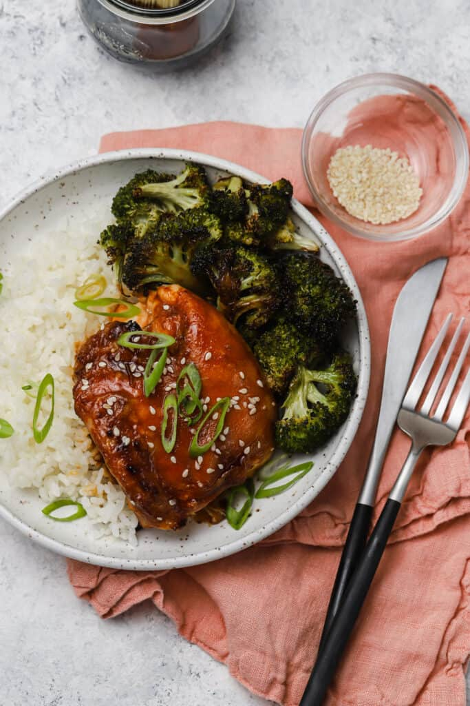 Baked chicken teriyaki with scallions white rice and broccoli on a white plate
