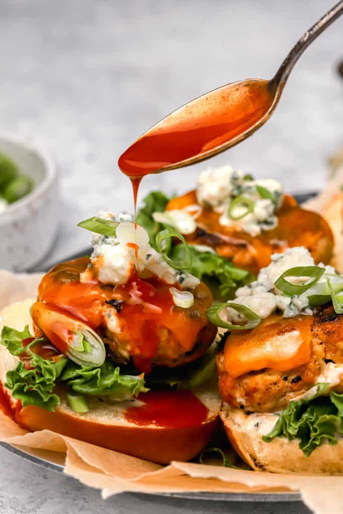 Buffalo wing sauce being spooned onto chicken sliders