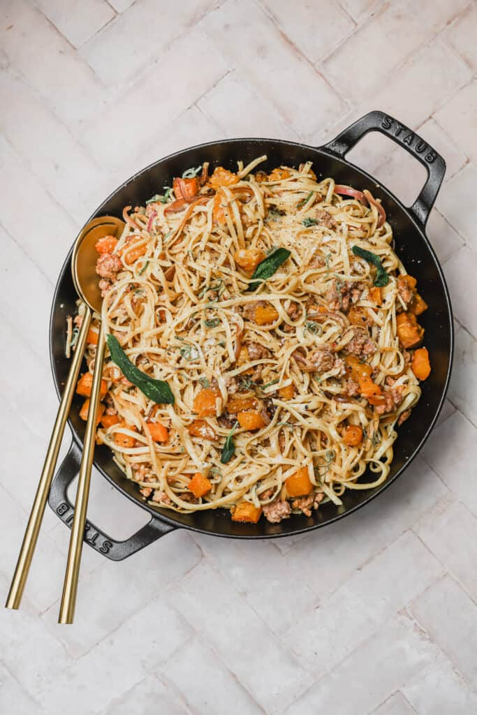 Chorizo and butternut squash pasta in a skillet with gold serving utensils
