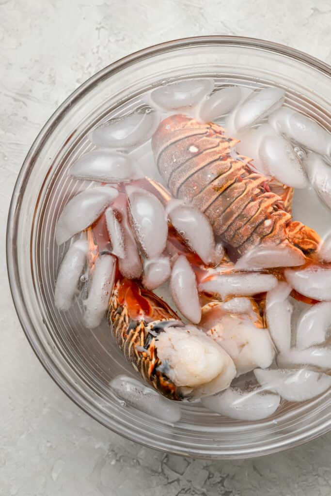 Parboiled lobster tails in an ice bath