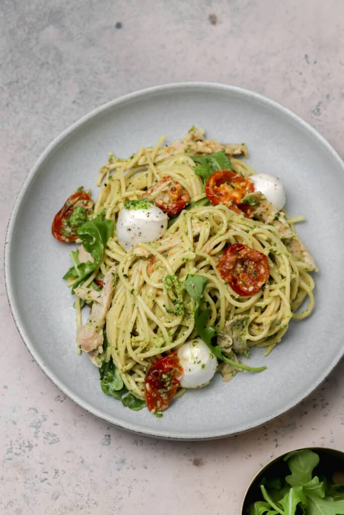 Pesto pasta on a plate with arugula tomatoes and mozzarella