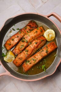 Salmon piccata with lemons in a skillet
