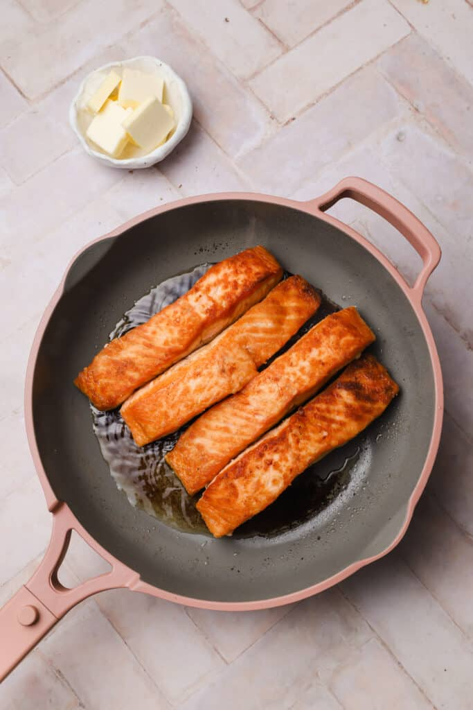 Seared salmon filets in a skillet