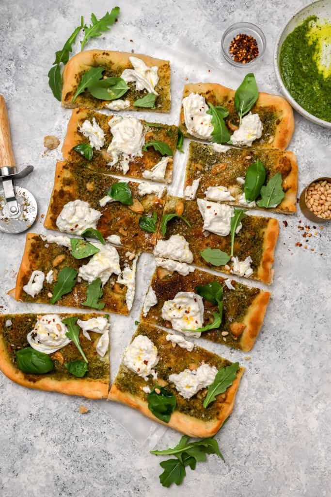 Sliced burrata pizza with arugula and red pepper flakes