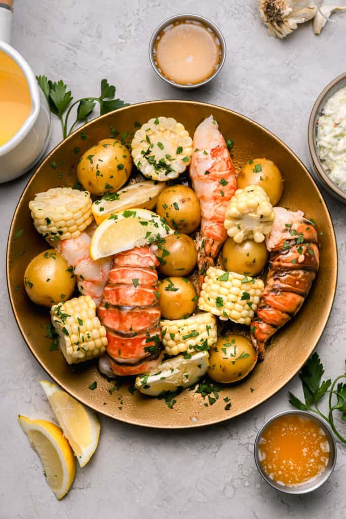 Sous vide lobster tails with potatoes and corn on a gold plate