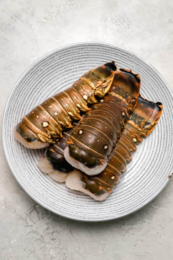 Uncooked lobster tails on a plate