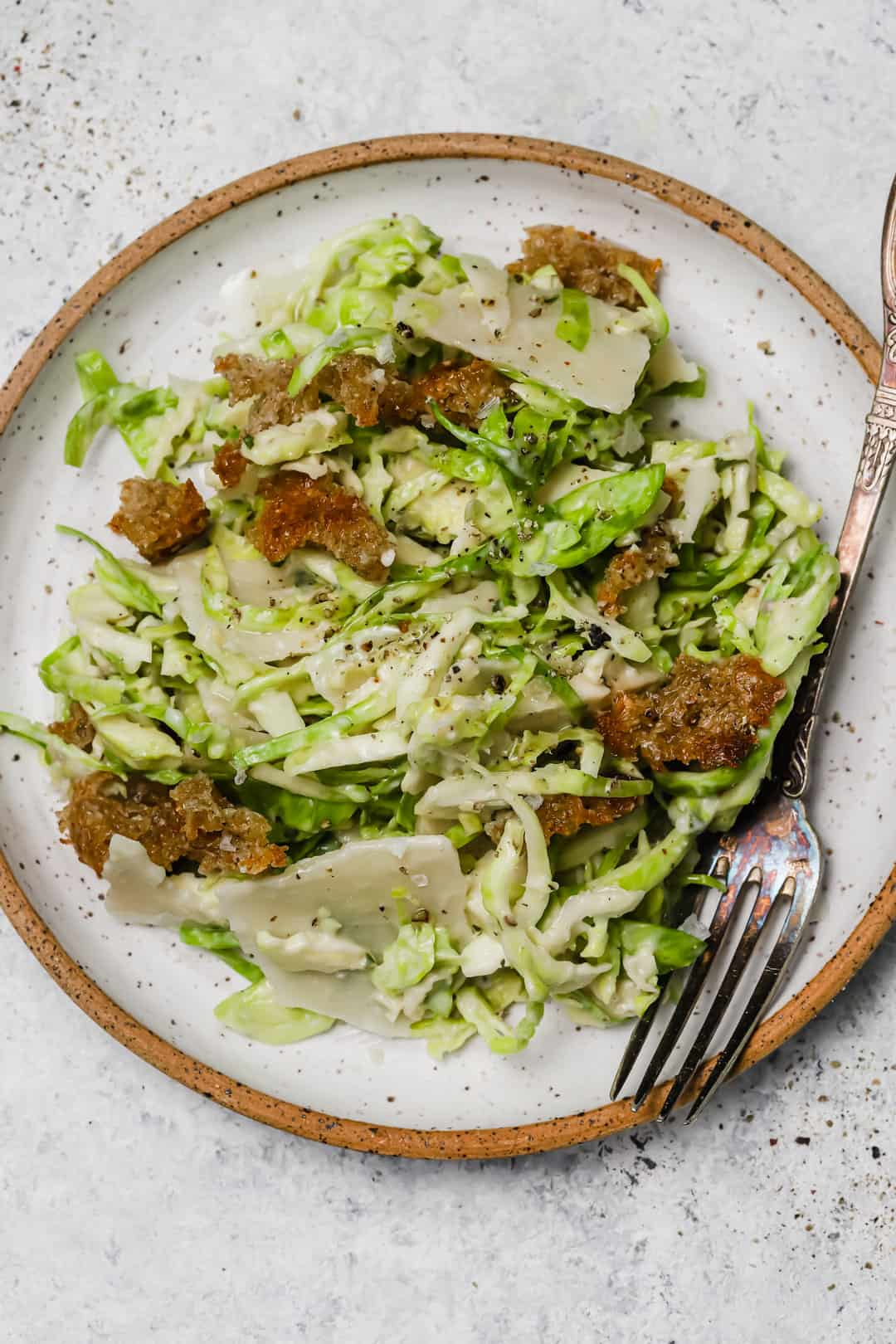 Brussel sprouts caesar salad on a plate with a fork