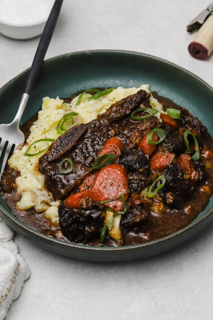 Flanken ribs with prunes and carrots on a plate with mashed potatoes