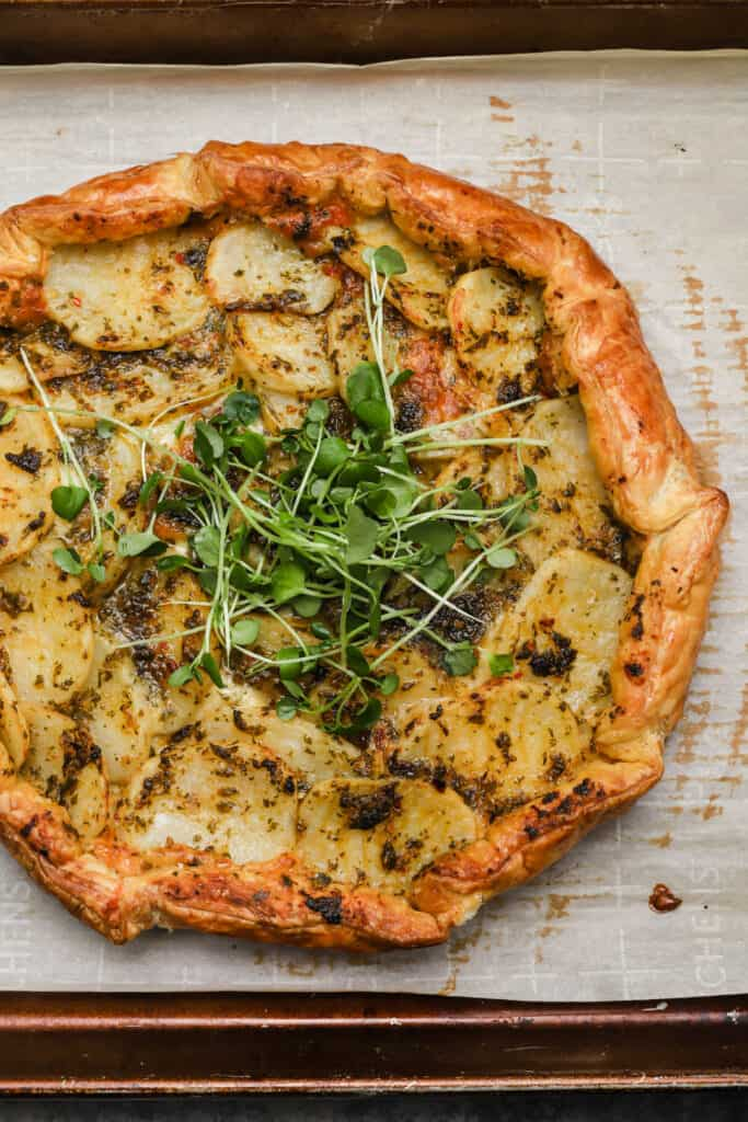 Galette topped with micro greens on a baking sheet