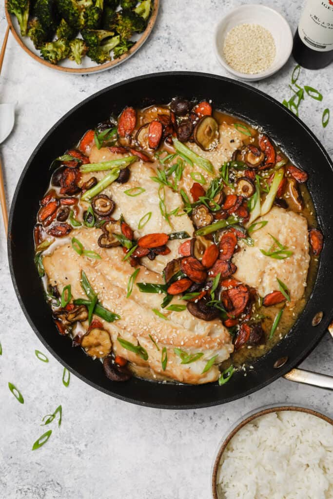Miso cod in a skillet with vegetables and sesame seeds