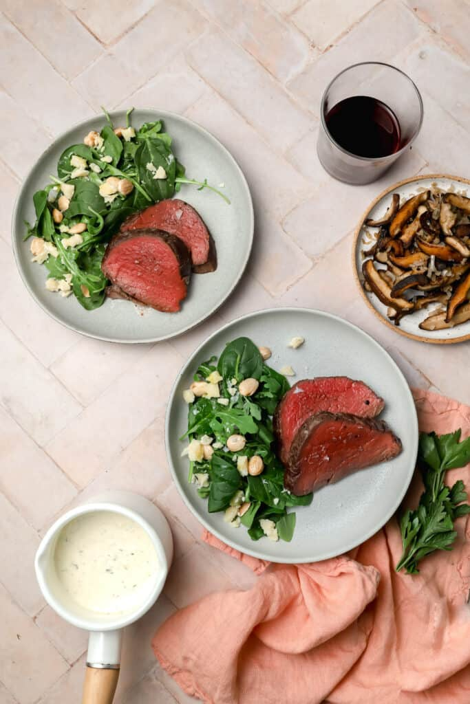 Plated beef tenderloin with spinach salad
