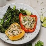 Stuffed peppers with ground chicken on a plate with broccolini