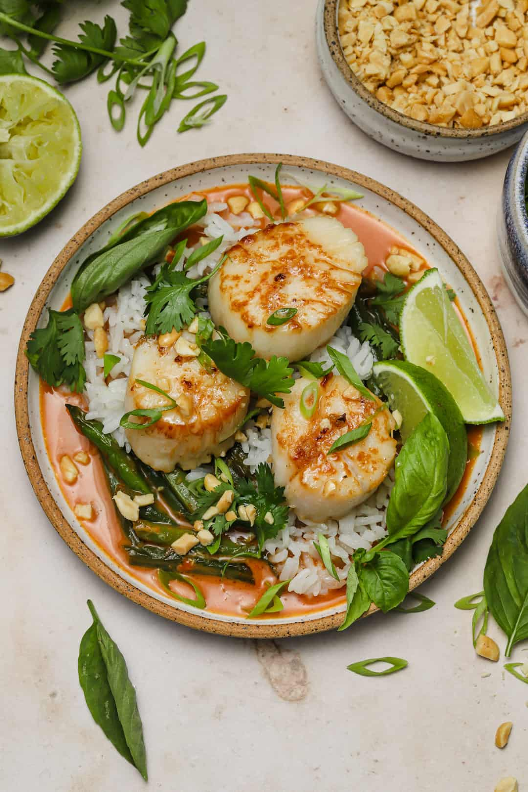 Thai scallop curry with rice and string beans on a plate with peanuts