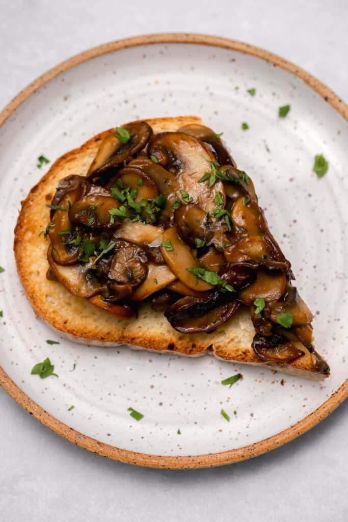 Close up of sautéed mushrooms on toast on a white plate