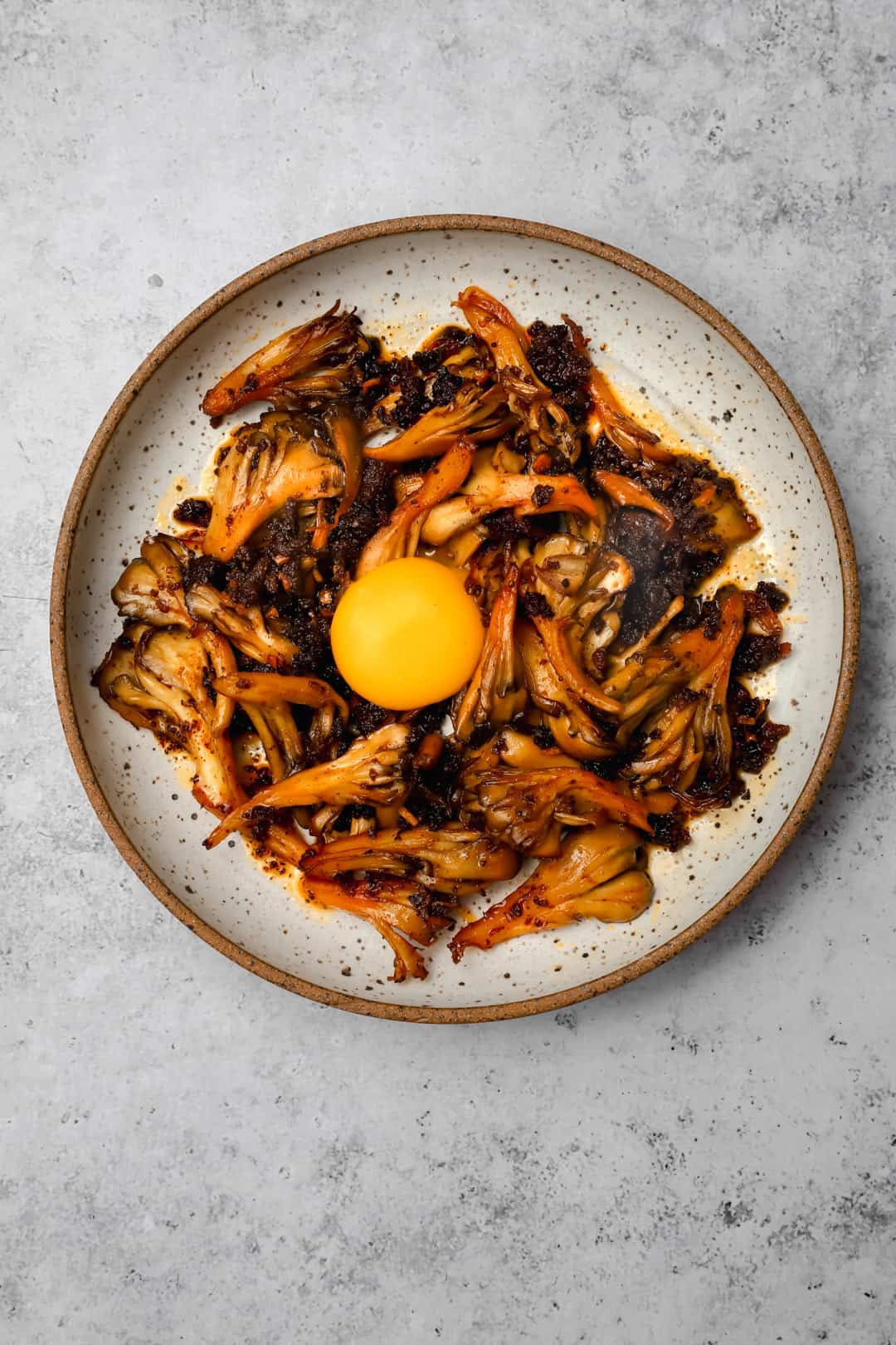 Hen of the wood mushrooms with an egg yolk on a plate