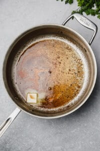 Melting butter into veal sauce in a pan