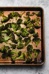 Roasted broccoli on a rimmed baking sheet