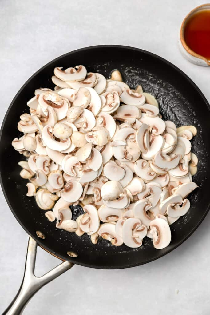 White button mushrooms cooking in a pan with butter