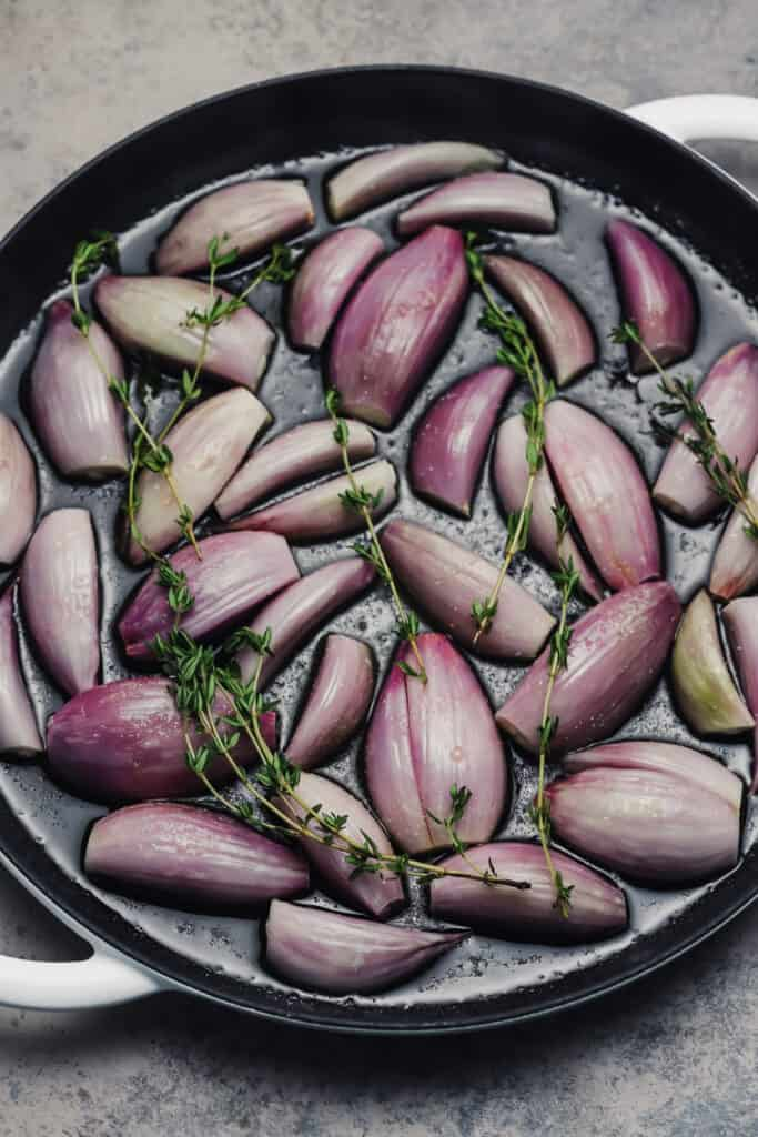 Halved shallots and thyme in a skillet