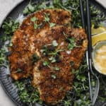 Pecan crusted chicken on a plate with lemon and micro greens