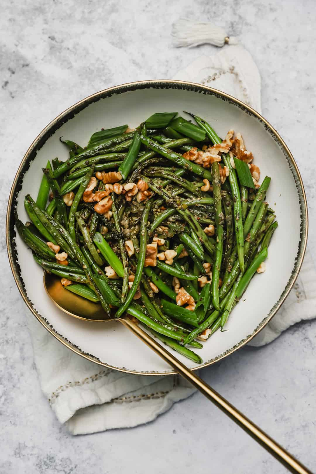 Sautéed French green beans with walnuts and capers in a bowl