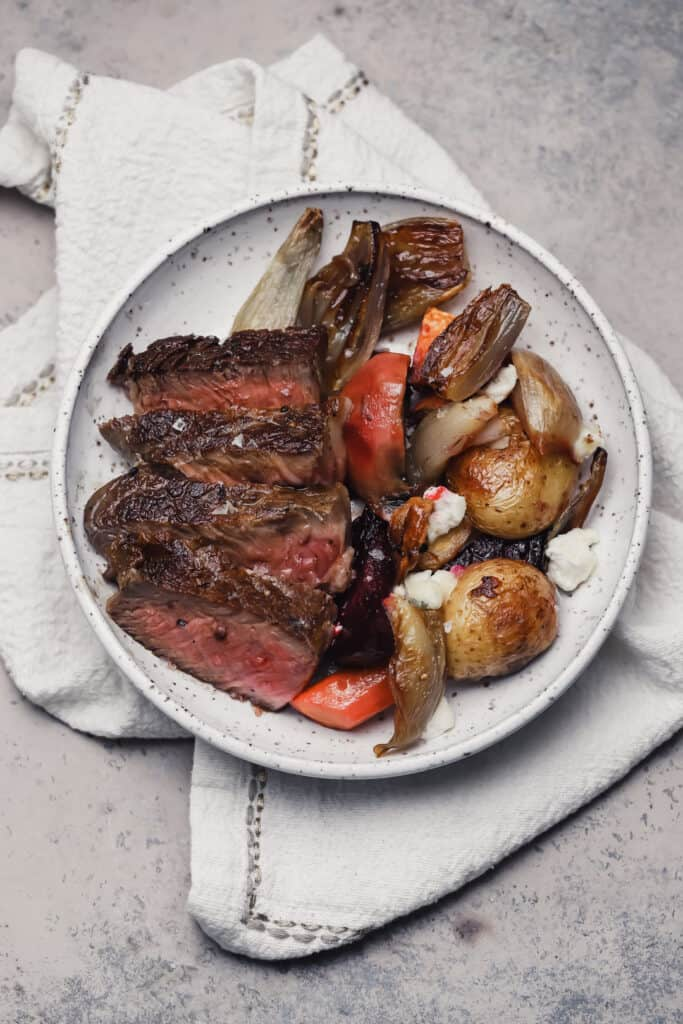 Steak with roasted veggies and shallots on a plate