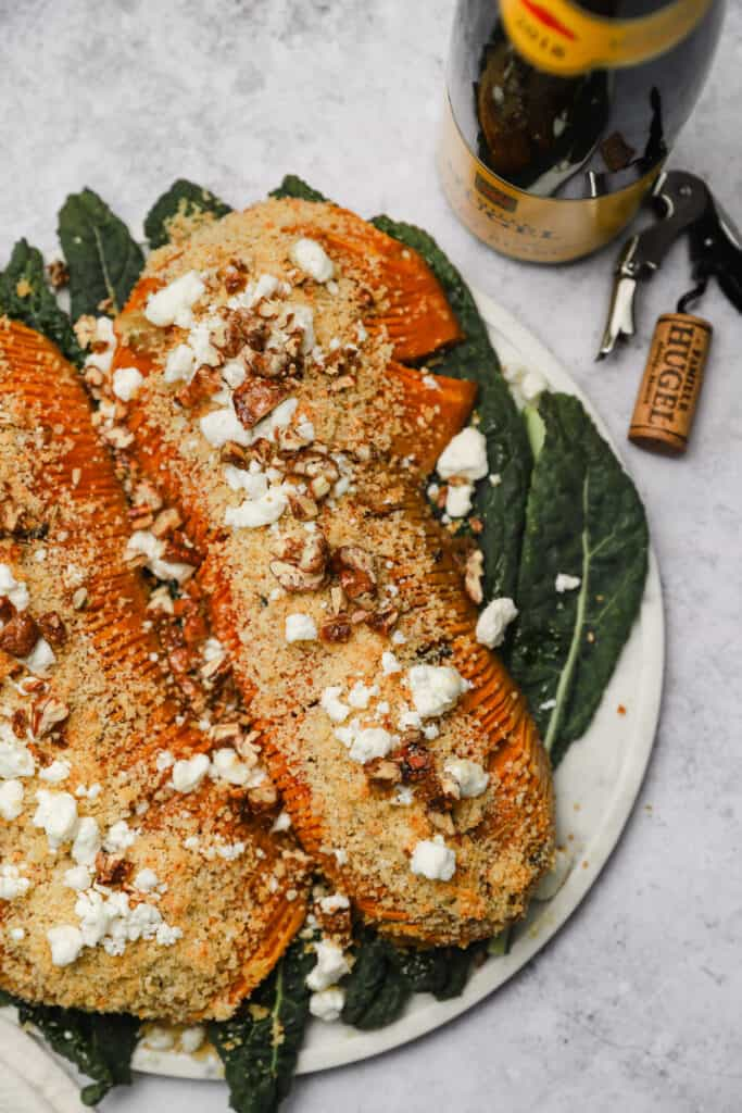 Two halved butternut squash on a tray with pecans and breadcrumbs