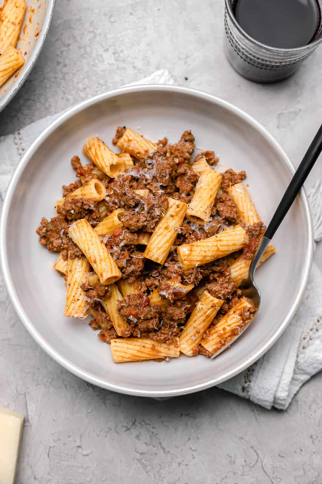 Big bowl of rigatoni bolognese with grated Parmesan