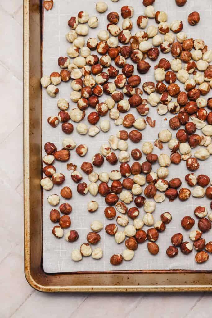 Raw hazelnuts on a baking sheet before roasting