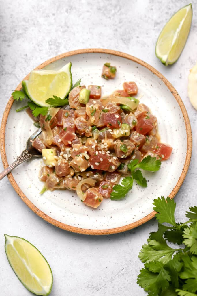 Raw marinated tuna on a plate with lime wedges