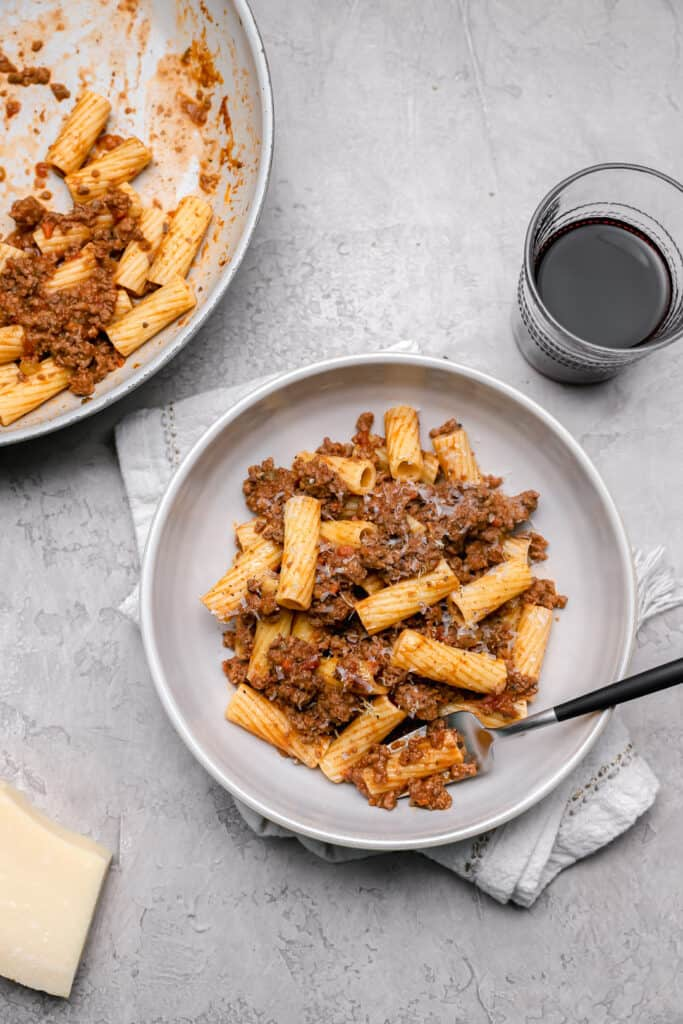 Skillet of rigatoni bolognese with a bowl of pasta on the side
