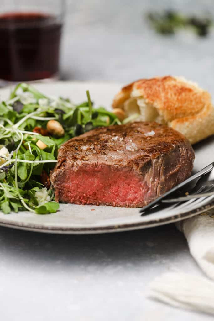 Sliced filet mignon on a plate with a salad