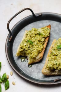 Bite of green olive tapenade on toasted baguette on a tray