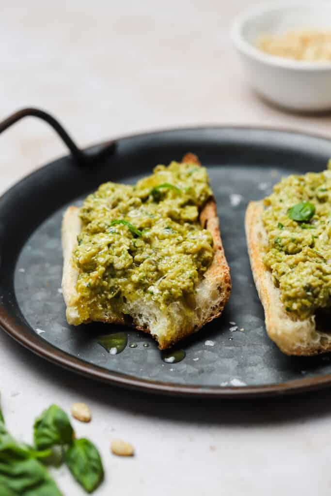 Green olive tapenade on toasted baguette on a tray