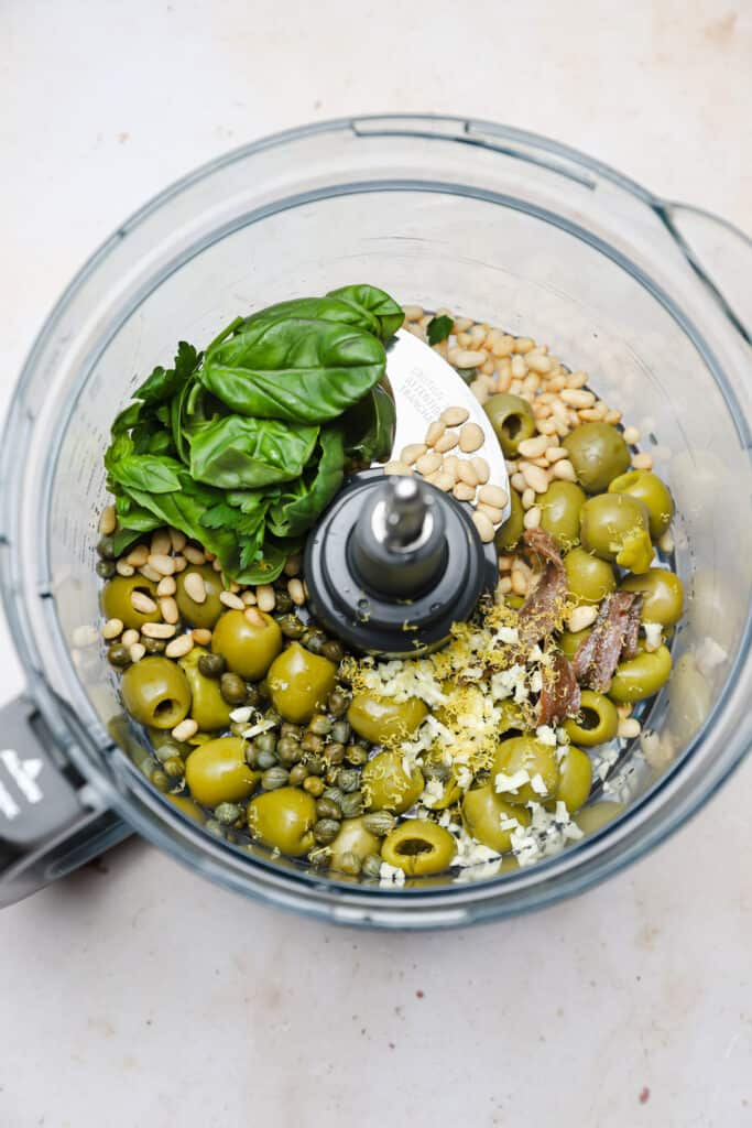 Olives capers anchovies and herbs in a food processor