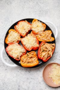 Stuffed buffalo chicken peppers with grated cheese in a pan