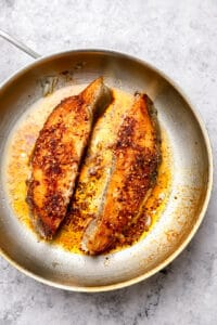 Halibut steaks with chili garlic oil in a skillet