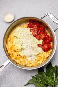 Pappardelle pasta with basil cream sauce and tomatoes in a skillet