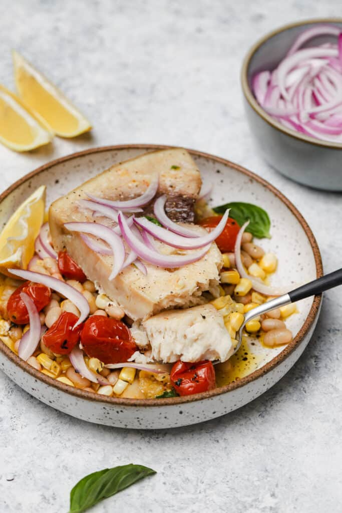 Baked fish with corn and white beans on a plate