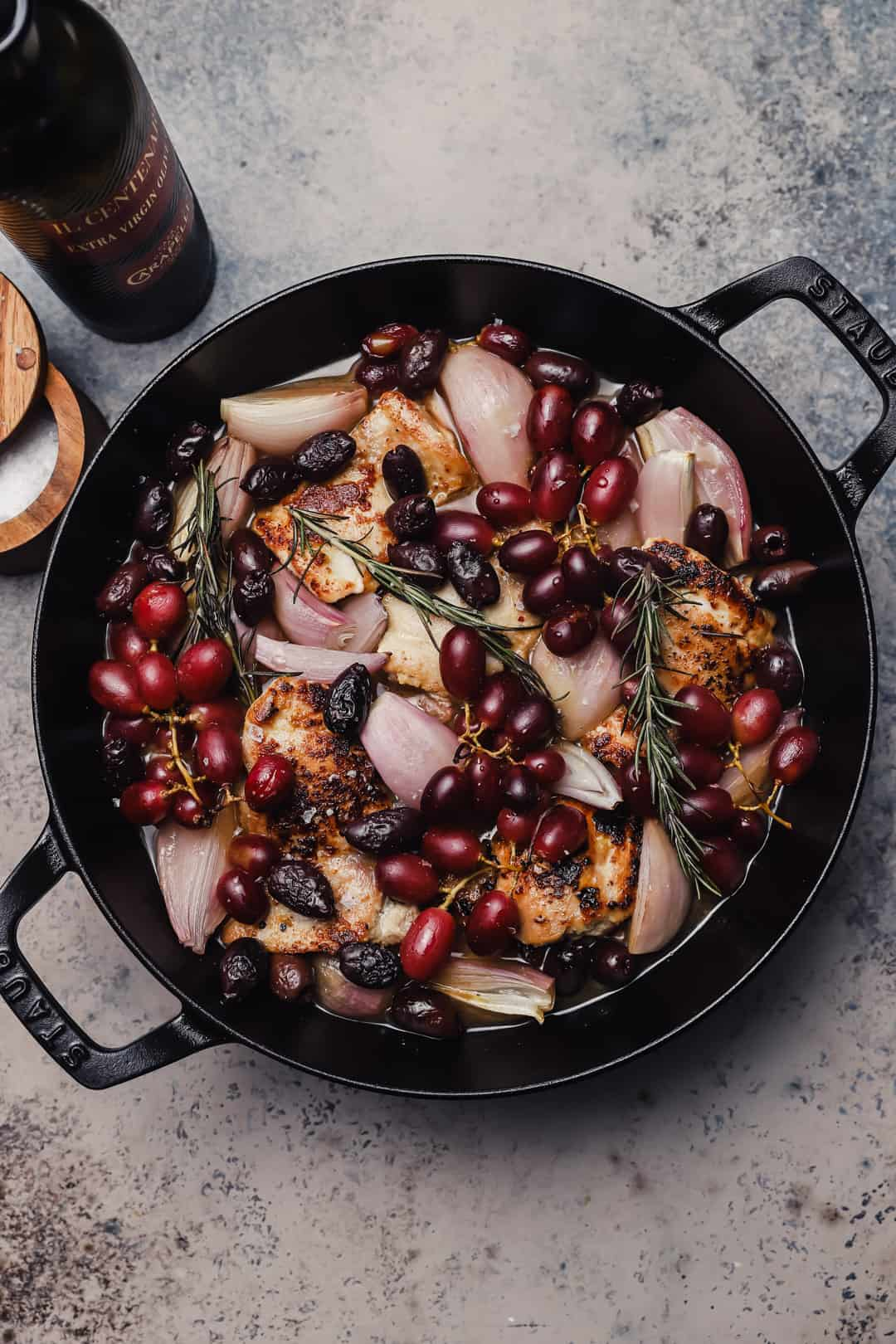 Chicken with olives grapes and shallots in a braiser