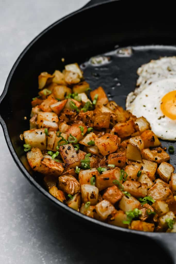 Diner style potatoes and onion with fried eggs in a cast iron skillet