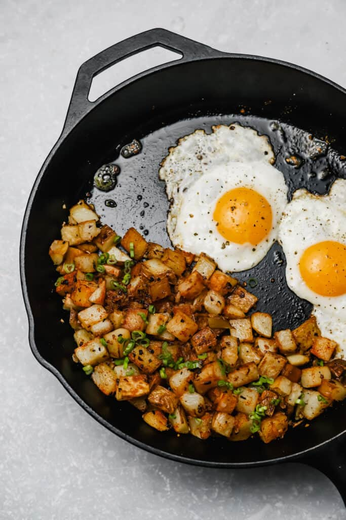 Fried potatoes and onion with fried eggs in a cast iron